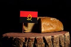 Angolanische Flagge auf einem Stumpf mit Brot Stockbilder