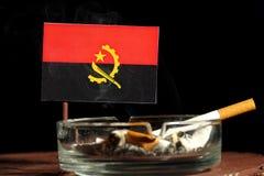 Angolanische Flagge mit brennender Zigarette im Aschenbecher lokalisiert auf Schwarzem Lizenzfreies Stockbild