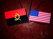 Angolanische Flagge mit USA-Flagge auf einem Baumstumpf Stockfotos