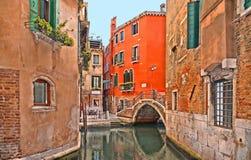 Angoli variopinti di Venezia, vecchie costruzioni e finestre, canale dell'acqua con le barche e piccolo ponte, Italia immagine stock libera da diritti