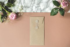 Angolo alto dello scrittorio rosa e di marmo sporco con le rose fresche, la busta di carta e gli spazi vuoti per i vostri taccuin fotografie stock