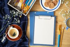 Angolo alto sulla tavola con il modello di carta accanto ai pennelli e della tazza di caffè immagine stock
