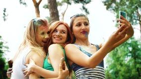 Angolo basso delle ragazze felici ridere e fare i selfies dopo il festival di Holi in parco video d archivio
