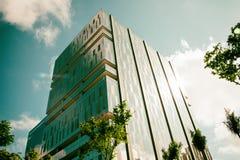 Angolo basso di una costruzione corporativa con l'effetto della luce dorato fotografia stock