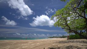 Angolo basso rapido della spiaggia di sabbia dell'oceano, nuvole fatte funzionare sul cielo, flash della gente sul contesto archivi video