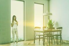 Angolo bianco della sala da pranzo, tavola nera, donna Fotografia Stock