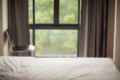 angolo della stanza del letto con la sedia e finestre e ciechi immagine stock