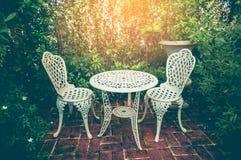 Angolo di rilassamento con la tavola e sedie nel giardino Annata e Immagine Stock Libera da Diritti
