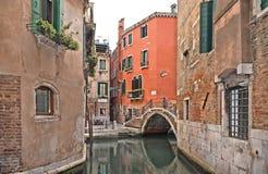 Angolo variopinto di Venezia con le vecchie costruzioni, il piccolo canale dell'acqua, poco ponte e le barche immagini stock libere da diritti