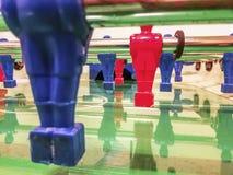 Angreifer einer roten und blauen Fußballtabelle in einem Spielraum stockfotografie