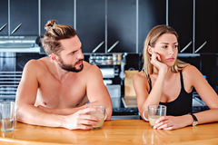 Angru couple sitting at the kitchen pult and holding coffee Royalty Free Stock Photography