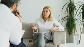 Angry adult woman talking about her problems with male psychoanalyst in his office. Indoors stock footage