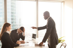 Angry african-american boss yelling at caucasian employees, scol. Angry bad african american boss yelling at caucasian employees, receiving reprimand with guilty Royalty Free Stock Photography
