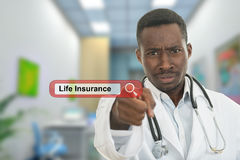Angry african black male doctor pointing finger at you with stethoscope around his neck. Life insurance search Stock Image