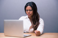 Angry african businesswoman using laptop Stock Photos