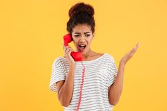 Angry african woman screaming while talking on red telephone. Isolated over yellow Royalty Free Stock Images