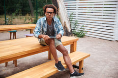 Angry african young man using tablet with earphones outdoors. Angry african young man in glasses using tablet with earphones outdoors Royalty Free Stock Photo