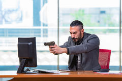 The angry aggressive businessman with gun in the office Stock Photos