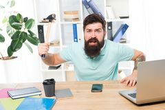 Angry aggressive businessman in office. Frustrated office worker holding hammer poised ready to smash. Office life makes. Him crazy. Businessman with beard and stock photos