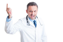 Angry aggressive doctor or medic threatening with syringe Stock Image