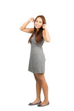 Angry Annoyed Asian Woman Temper Tantrum At Full. Teeth clenched Asian woman in gray dress with light brown hair, balled fists, looking at camera throwing Royalty Free Stock Image