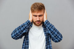 Angry annoyed bearded man covering ears with palms royalty free stock photos