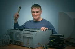 Computer technician. Angry and annoyed computer repairman beats the desktop computer with a hammer stock photo