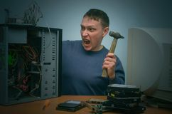 Computer technician. Angry and annoyed computer repairman beats the desktop computer with a hammer stock images