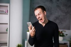 Angry annoyed man talking by phone, shouting guy. Angry annoyed man talking by phone. shouting guy. Exaggerated negative emotion royalty free stock photo