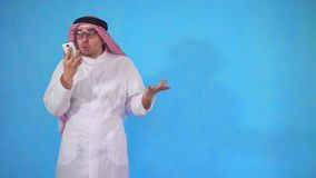 Angry Arab man impulsively talking on the phone standing on a blue background. Angry Arab man with glasses impulsively talking on the phone standing on a blue stock footage