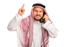 Angry Arab talking on telephone. Studio shot of an angry Arab talking on telephone and threatening with his finger isolated on white background Royalty Free Stock Image