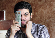 Angry arab young businessman with dollar bill money. Arab young muslim business man feeling sad and angry with dollar bills on one of his eye Stock Photography