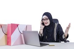 Angry Arabic woman talking on the cellphone. Portrait of Arabian woman looks angry while talking on mobile phone with laptop and shopping bags on the table Stock Image