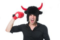 Angry as bull. Man shouting face wears hat of devil or bull with horns. Guy black shirt angry aggressive demonstrate. Strength gesture with boxing glove. Guy royalty free stock images