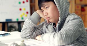 Angry asian boy doing your homework with feel anxious about, worry and be tired. Dolly move left to right.