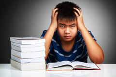 Angry asian boy with learning difficulties. Grey background Stock Photos
