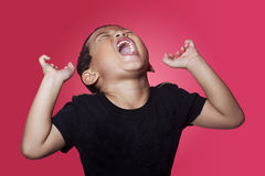 Angry Asian boy over red background. Shouting angry asian kid on red background Stock Photos