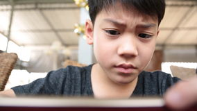 Angry asian boy playing game on your mobile phone stock video footage