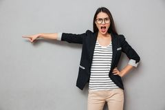 Angry asian business woman in eyeglasses with arm on hip. Pointing away and looking at the camera over gray background royalty free stock images
