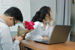 Angry Asian businesswoman refuses a bouquet of red roses from business man. Disappointed love concept. Stock Image