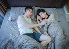 Angry Asian couple fighting on bed at night Stock Images