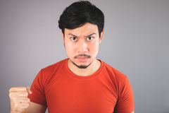 Angry Asian man with oily face. Angry Asian man with oily face in red T-shirt Royalty Free Stock Images