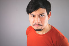 Angry Asian man with oily face. Angry Asian man with oily face in red T-shirt Royalty Free Stock Photography