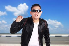 Angry Asian Man Pointing to Camera. Angry Asian man wearing black leather jacket and sunglasses shows cynical unhappy angry facial expression pointing to camera Stock Images
