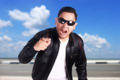 Angry Asian Man Pointing to Camera. Angry Asian man wearing black leather jacket and sunglasses shows cynical unhappy angry facial expression pointing to camera Stock Photos