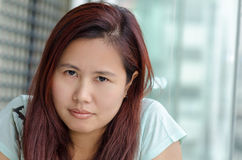 Angry Asian woman. Portrait of Asian woman who is sitting next to window glass and looking to camera Stock Photos