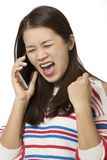 Asian woman talking on a smartphone isolated on white background. Angry Asian woman talking on a smartphone isolated on a white background Stock Photography