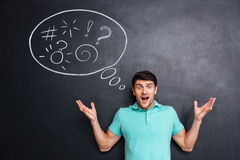 Angry astonished man shouting over blackboard background with speech bubble Stock Photo