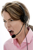 Angry Attractive Young Business Woman Using a Telephone Headset stock photography
