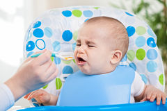 Angry baby doesn't like fruit mash. Feeding problems Royalty Free Stock Photo